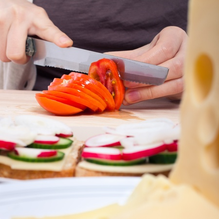 Detail of kitchen table female hands slicing fresh tomato. Stock Photo - 13106341