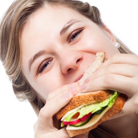 Close up of beautiful young happy woman eating sandwich. photo