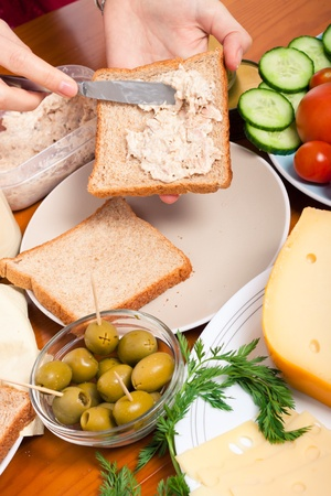 sandwich spread: Detail of kitchen table with food and female hands making tuna sandwich.