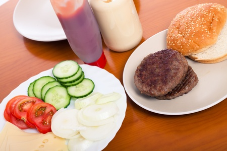 Detail of kitchen table with hamburgers and vegetable. Stock Photo - 13106630