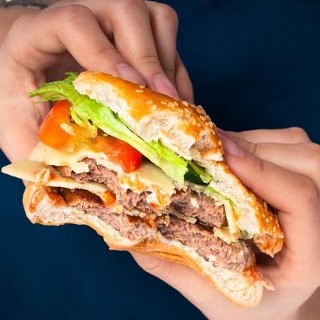 Close up of hands holding hamburger, over dark blue background. photo