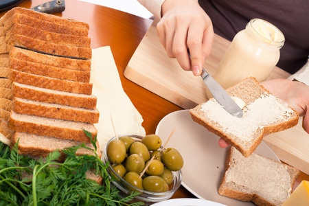 mahonesa: Detalle de la mesa de la cocina y las manos femeninas propagación sándwich de mayonesa de elaboración. Foto de archivo