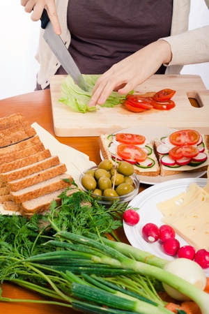 Detail of kitchen table and woman cutting fresh vegetable and making sandwiches. Stock Photo - 13222739