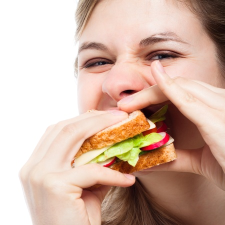 Close up of hungry woman eating sandwich, isolated over white background. photo