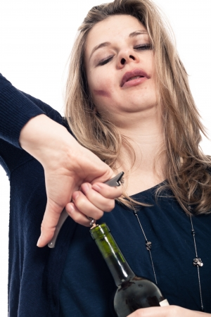 opener: Close up of young drunk woman opening bottle of wine, isolated on white background.