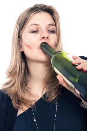 drug addiction: Portrait of drunk woman drinking bottle of wine, isolated on white background.