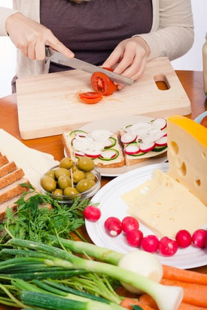 Detail of kitchen table with vegetable, sandwiches and female hands cutting fresh tomato. photo