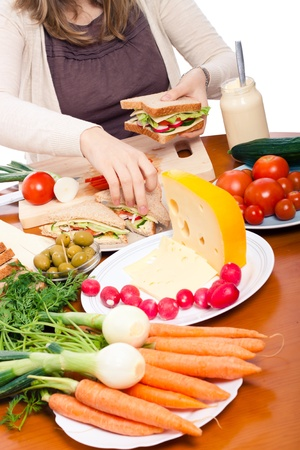 Detail of kitchen table and woman preparing fresh vegetable sandwiches. photo