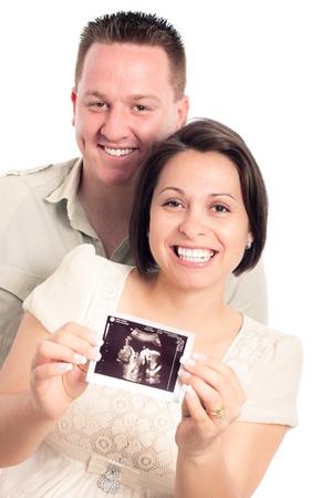 sonograma: Feliz mujer embarazada con su marido, que muestra imágenes de ultrasonido del bebé, aisladas sobre fondo blanco