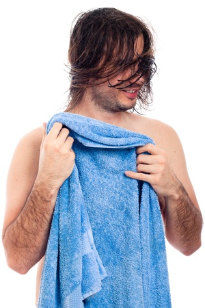 Young man after bath going to dry his long hair with blue towel, isolated on white background. photo