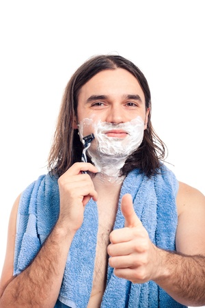 Young longhaired happy man shaving after bath, isolated on white background. photo