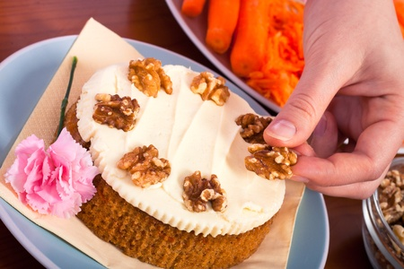 carrot cake: Close up of decorating carrot cake with walnuts. Stock Photo