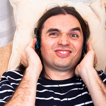 Young funny man with headphones listening music on sofa. Stock Photo - 13584769