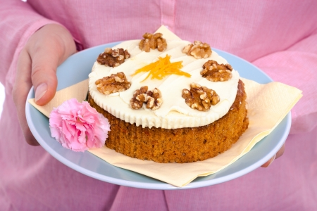 Delicious whole carrot cake with icing, grated carrots and walnuts on pink background. photo