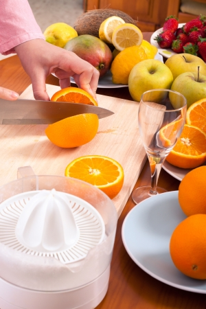 Detail of hand cutting oranges and preparing fresh homemade orange juice. photo
