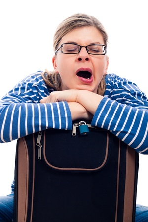 Tired traveller tourist woman yawning on luggage, isolated on white background. photo