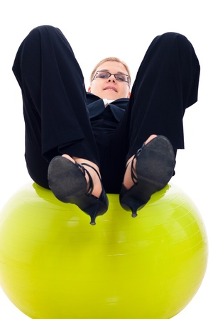 Businesswoman having fun on green exercise ball, isolated on white background. photo