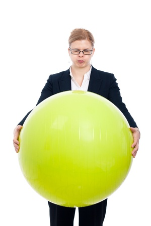 Funny bloated businesswoman holding green exercise ball, isolated on white background.