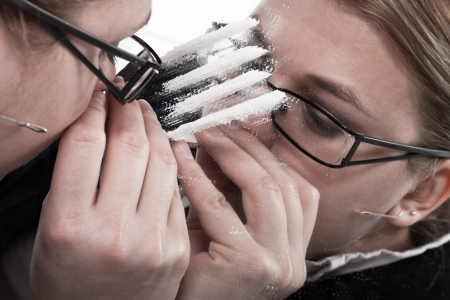 Drug addicted businesswoman reflected in mirror snorting line of cocaine. Stock Photo