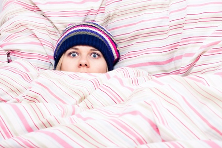 pattern bed: Scared woman in winter hat hiding wrapped in duvet.