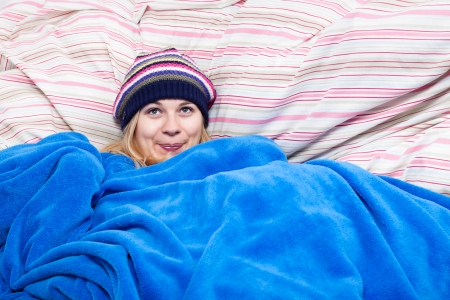 striped pajamas: Joven mujer feliz lindo en sombrero de invierno envuelto en un edred�n. Foto de archivo