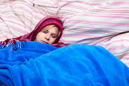 striped pajamas: Young woman sleeping wrapped in a duvet.
