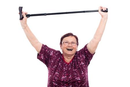 Happy laughing elderly woman holding walking stick, isolated on white background. Stock Photo