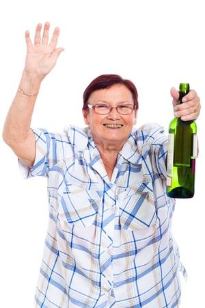 tipsy: Elderly happy drunk woman with bottle of alcohol, isolated on white background. Stock Photo