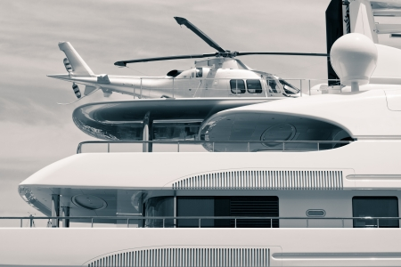 luxurious lifestyle: Luxury yacht with helicopter on the deck, digitally retouched and toned photo.