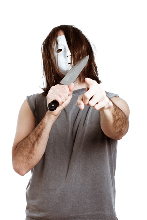 Scary weird masked man with knife, pointing at you, isolated on white background. photo