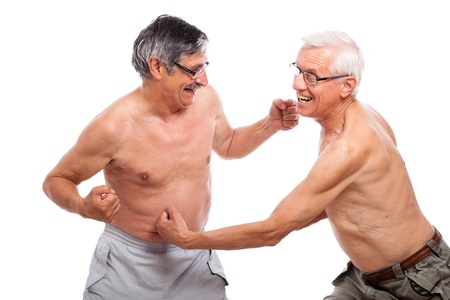 Two funny seniors fighting, isolated on white background. photo