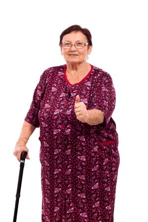 senioren wandelen: Portret van gelukkige lachende senior vrouw met duim omhoog, geïsoleerd op een witte achtergrond.