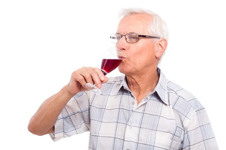 Senior man drinking glass of red wine, isolated on white background.