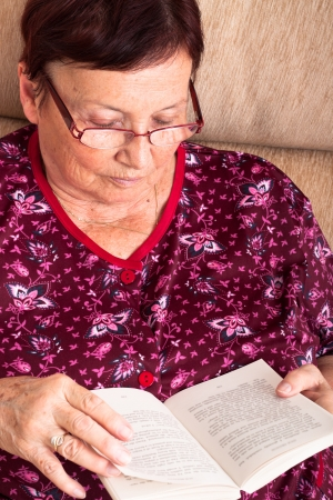 Close up of senior woman sitting on sofa and reading book. photo