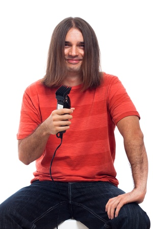 Happy smiling long haired young man holding hair trimmer, isolated on white background.