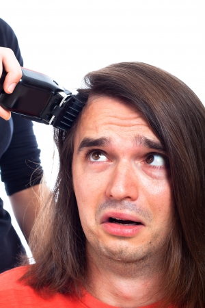 Close up of unhappy long haired man being shaved with hair trimmer, isolated on white background. photo