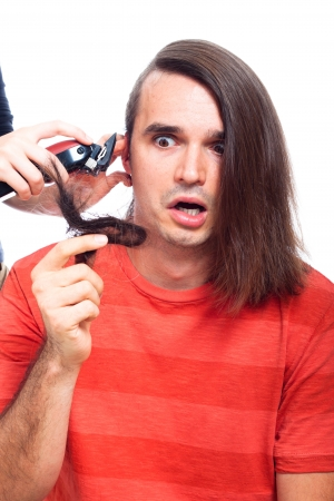 Shocked long haired man being shaved with hair trimmer, isolated on white background. photo