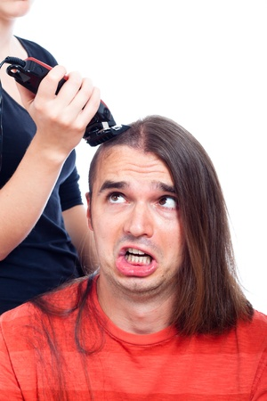Unhappy long haired man being shaved with hair trimmer, isolated on white background. photo