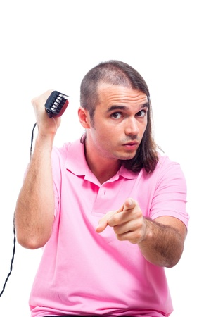 Half bald young man with hair trimmer pointing at you, isolated on white background. photo