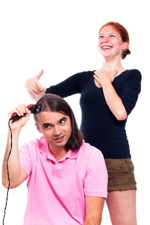 Young man shaving his head with hair trimmer and woman laughing at him, isolated on white background. Stock Photo - 14715640