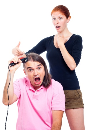 Shocked long haired man screaming, shaving his head with hair trimmer and woman pointing at him, isolated on white background. Stock Photo - 14715628