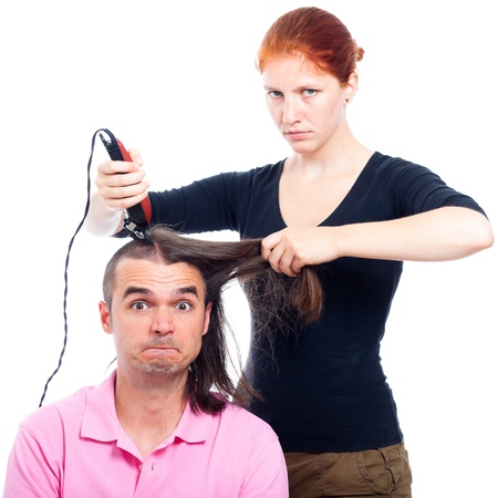 Serious hairdresser woman shaving funny long haired man with hair trimmer, isolated on white background.