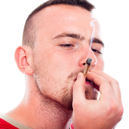 drug dealers: Close up of young man smoking hashish joint, isolated on white background. Stock Photo