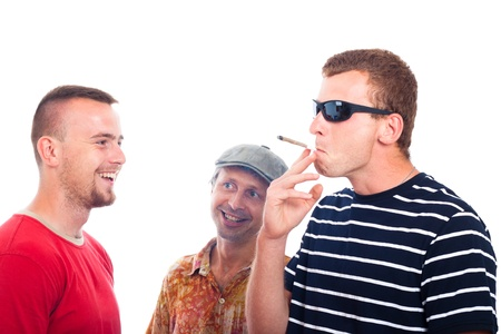 Three young smiling guys smoking hashish joint, isolated on white background. Stock Photo - 14715632