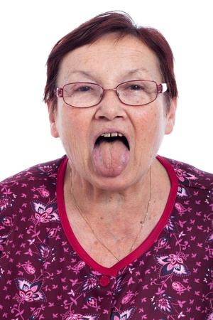 Funny senior woman sticking out tongue, isolated on white background. photo