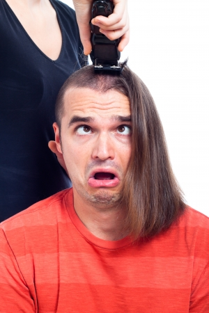 Close up of shocked long haired man being shaved with hair trimmer, isolated on white background. photo