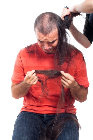 Unhappy bald man holding his long hair man and crying, being shaved with hair trimmer, isolated on white background. photo