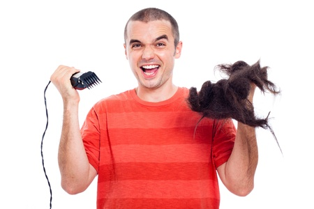 Funny bald man holding his long shaved hair and hair trimmer, isolated on white background. photo