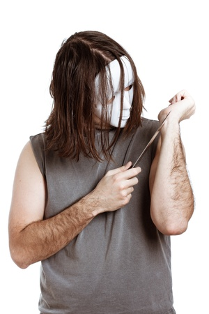 self harm: Scary masked psycho man with knife attempting suicide, isolated on white background. Stock Photo