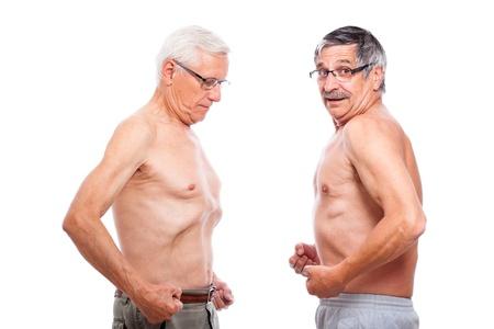 Two seniors comparing figure, isolated on white background. photo